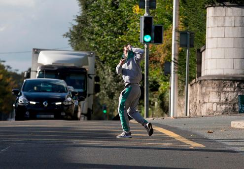 Ross Hutch tries to hide his face as he runs into the road to avoid photographers while leaving Dublin District Court. Photo: Collins Courts