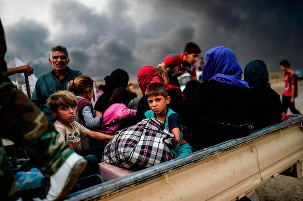 Iraqi families who were displaced by the ongoing operation by Iraqi forces against jihadistds of the Islamic State group to retake the city of Mosul, are seen gathering in an area near Qayyarah on October 24, 2016. / AFP PHOTO / BULENT KILICBULENT KILIC/AFP/Getty Images