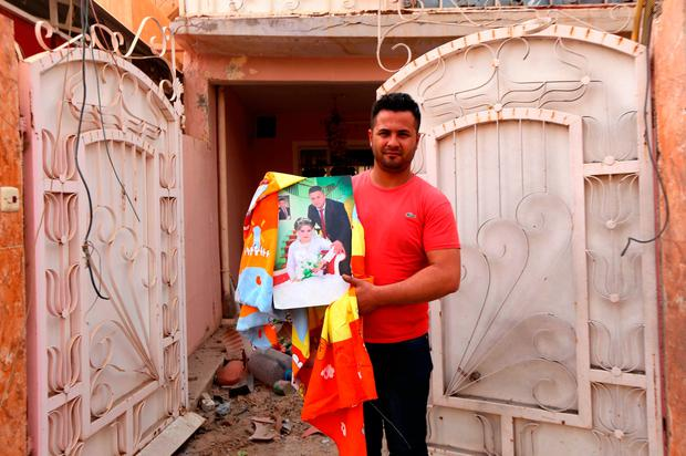 An Iraqi man shows his wedding picture outside his house on October 24, 2016 in the Christian Iraqi town of Bartella, about 15 kilometres (10 miles) east of Mosul, after Iraqi forces retook control of the town from jihadists of the Islamic State group. / AFP PHOTO / SAFIN HAMEDSAFIN HAMED/AFP/Getty Images