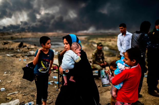 Iraqi families, who were displaced by the ongoing operation by Iraqi forces against jihadistds of the Islamic State group to retake the city of Mosul, are seen gathering on an area near Qayyarah on October 24, 2016. / AFP PHOTO / BULENT KILICBULENT KILIC/AFP/Getty Images