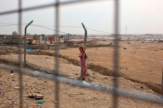 A girl stands inside a camp for displaced families in Dibaga, near Mosul, Iraq, Monday, Oct. 24, 2016.(AP Photo/Marko Drobnjakovic)