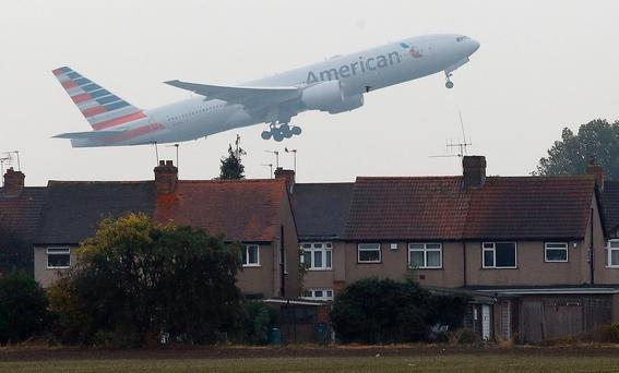 An airplane takes off over the rooftops of nearby houses at Heathrow Airport in Harmondsworth. Photo: AP