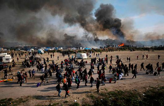 People walk past as thick smoke and flames rise from amidst the tents after fires were started in the makeshift migrant camp known as