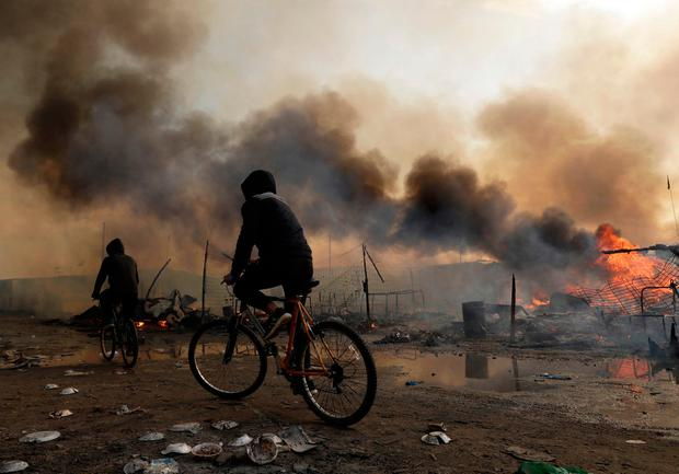 Migrants ride past burning shelters set on fire in the makeshift migrant camp known as