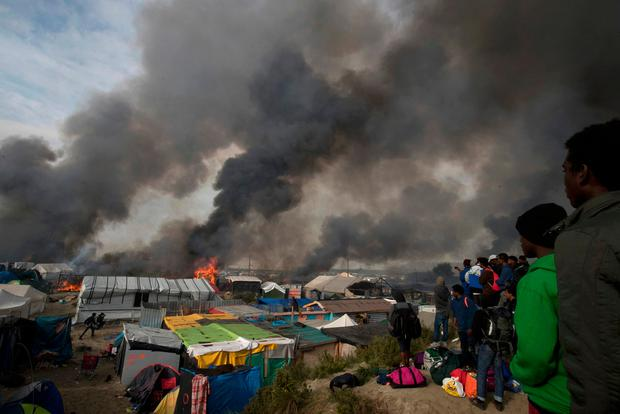 Migrants look at burning makeshift shelters and tents in the