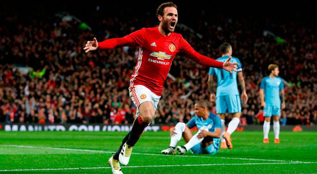 Juan Mata wheels away after scoring the only goal for Manchester United in last night's League Cup victory over Manchester City last night. Photo: Martin Rickett/PA Wire