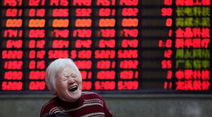 An investor reacts in front of an electronic board showing stock information at a brokerage house in Shanghai, China. Photo: Reuters