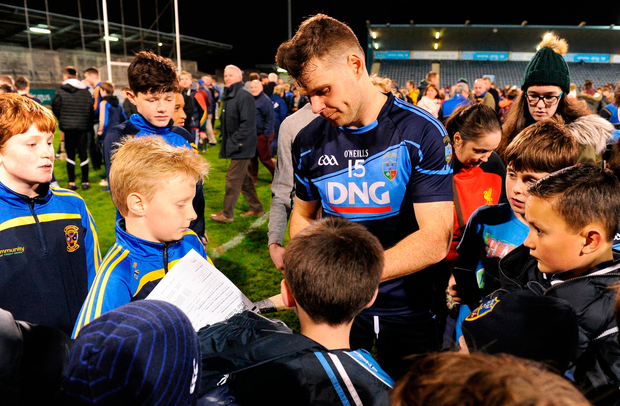Kevin McManamon of St Jude's signs autographs for supporters despite his team losing