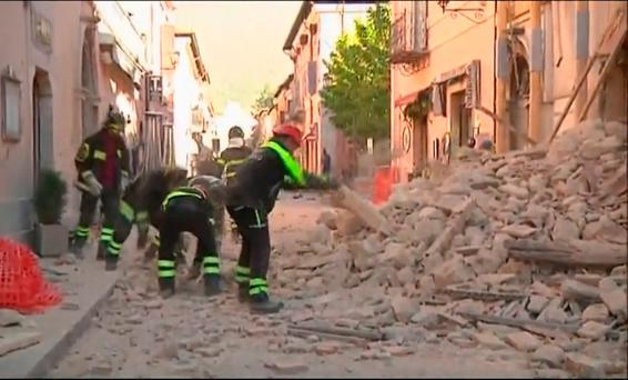 In this image made from video, firefighters clean rubbles fallen from a damaged building in Norcia, Italy, Sunday, Oct. 30, 2016 after a powerful earthquake with a preliminary magnitude of 6.6 rocked central and southern Italy following a week of temblors left thousands homeless. (Sky Italia via AP)