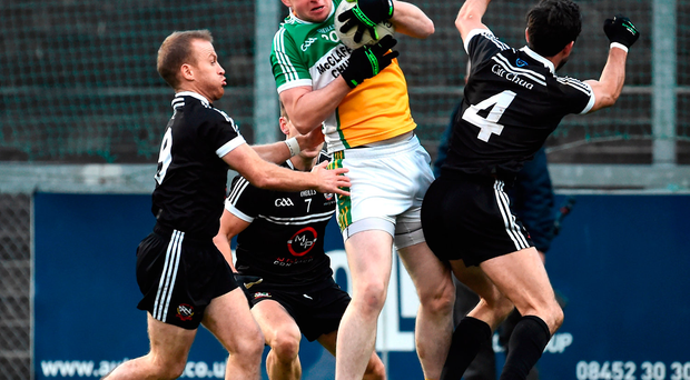 Christopher McMonigle of Glenswilly in action against Gerard McEvoy, Aaron Branagan and Niall Branagan of Kilcoo