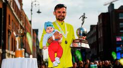 Sergiu Ciobanu from Co Tipperary with his son Daniel, age 4 months, after winning the men's Irish National Championship. Photo by Stephen McCarthy/Sportsfile