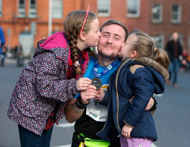 Jonathan Smart, from Finglas, gets a kiss from daughters Emma and Sophie. Photo: Damien Eagers