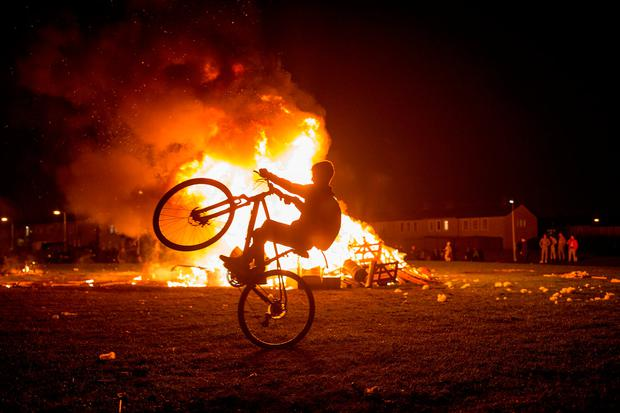 A youngster pulls a wheelie alongside a bonfire in Darndale in Dublin. Photo: Arthur Carron