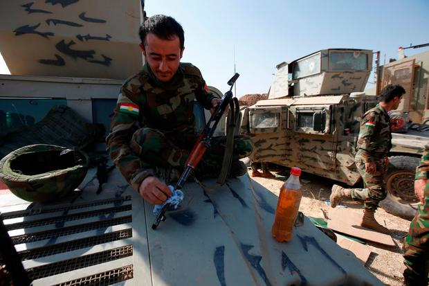 A member of Peshmerga forces cleans his weapon on the outskirts of Bashiqa, east of Mosul. Photo: Azad Lashkari