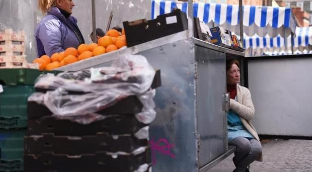 A woman arranges her stall as she chats to her friend at the Moore Street fruit and vegetable market in Dublin, Ireland April 23, 2016. REUTERS/Clodagh Kilcoyne - RTX2BC22
