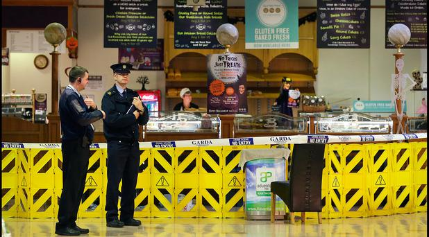 A Garda and a security man at Longford Shopping Centre where the victim was found. Pic Steve Humphreys