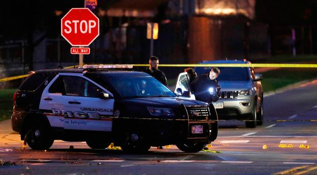 Police officers gather evidence at the scene of a shooting, Wednesday (AP Photo/Charlie Neibergall)