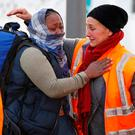 A volunteer hugs a migrant woman as she leaves the Jules Ferry center to take a bus for their transfer by French authorities to reception centres across the country during the dismantlement of the camp called the 'Jungle' in Calais, France. Photo: REUTERS/Pascal Rossignol