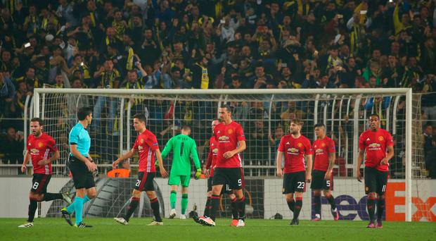 Manchester United players walk after Fenerbahce Jeremain Lens scored his team's second goal