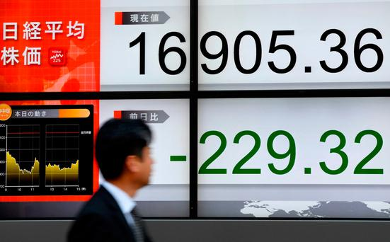 A pedestrian walks past an electronic stock indicator in the window of a security company in Tokyo. Photo: AFP/Getty Images