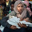 A young woman holds her baby aboard the Topaz Responder, a rescue ship run by Maltese NGO
