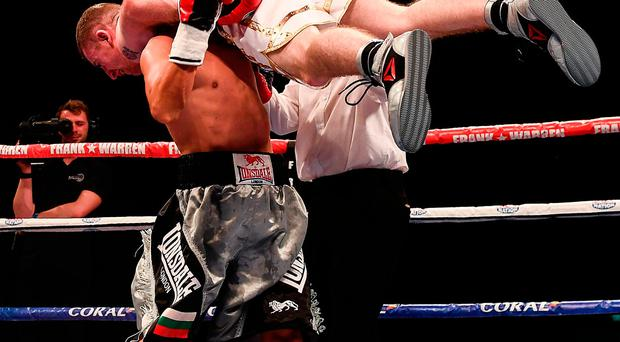 Paddy Barnes is lifted by Stefan Slavchev in the fourth round, resulting in the stoppage of their flyweight bout at the Titanic Exhibition Centre in Belfast. Photo by Ramsey Cardy/Sportsfile