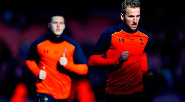 Harry Kane of Tottenham Hotspur (R) warms up prior to the Premier League match between Arsenal and Tottenham Hotspur at Emirates Stadium