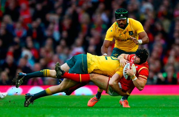 Wales' Leigh Halfpenny is tackled by Australia's Reece Hodge. Photo: Getty