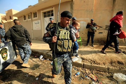 A member of Iraqi security forces carries a child as displaced people who fled Hammam al-Alil, south of Mosul, head to safety Picture: Reuters