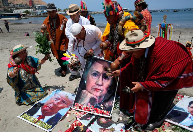 Peruvian shamans with posters of U.S. presidential candidates Hillary Clinton and Donald Trump perform a ritual of predictions ahead of the U.S. presidential elections, at Lima, Peru November 7, 2016. REUTERS/Mariana Bazo