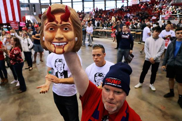 A man holds a mask of Hillary Clinton at a campaign rally for Donald Trump in Raleigh, North Carolina Picture: Getty
