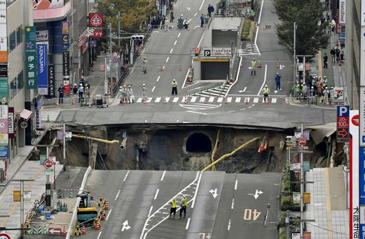 A massive shinkhole is created in the middle of the business district in Fukuoka, southern Japan. (Sadayuki Goto/Kyodo News via AP)