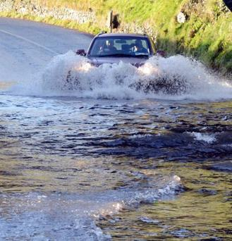 A car trying to make its way through the flood waters on the Ballinrobe Road in Westport after Storm Desmond hit Picture: Paul Mealey