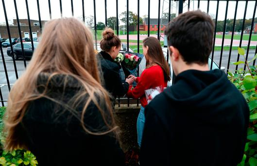 (left to right) Alanna Goddard, 17, Hannah Jacobs, 18, Grace Jacobs,18, and Luke Wilton, 17, lay flowers at the scene in Queen's Avenue, Aldershot, where two teenage girls died after being struck by a car while jogging Credit: Andrew Matthews/PA Wire