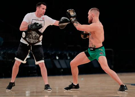 Conor McGregor, right, works out ahead of his UFC 205 mixed martial arts bout against Eddie Alvarez during an open workout, Wednesday, Nov. 9, 2016, at Madison Square Garden in New York. McGregor will square off against Alvarez during their match on Saturday. (AP Photo/Julio Cortez)
