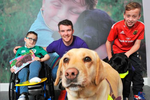 Munster player Peter O'Mahony with Cian Hennessey (8) from Togher, Co Cork, and Darragh O'Regan (12) from Mallow, Co Cork, launching the Dogs for the Disabled calendar. Pic Daragh Mc Sweeney / Provision