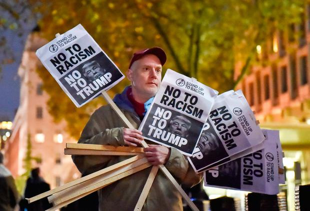 A man holds placards at an anti-racism protest against U.S. President-elect Donald Trump outside of the U.S Embassy in London, Britain, November 9, 2016. REUTERS/Hannah McKay