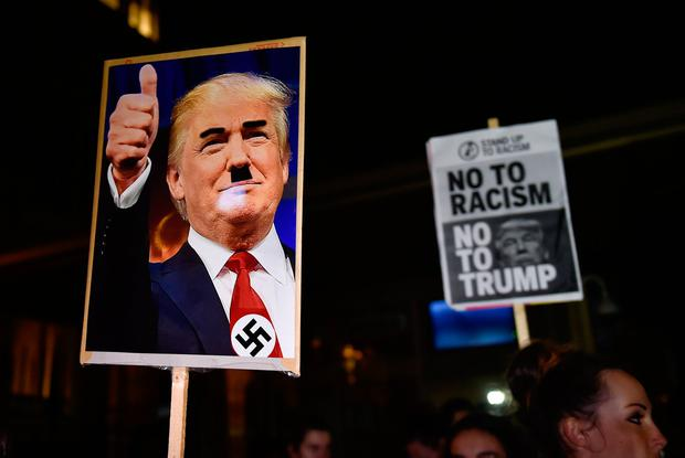 People hold placards at an anti-racism protest against U.S. President-elect Donald Trump outside of the U.S. Embassy in London, Britain, November 9, 2016. REUTERS/Hannah McKay