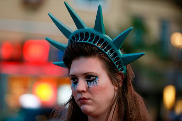 A demonstrator wears a headpiece depicting the crown of the Statue of Liberty during a protest in San Francisco, California, U.S. following the election of Donald Trump as the president of the United States November 9, 2016. REUTERS/Stephen Lam