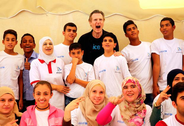 Liam Neeson, back row in black, yells as he poses for a group photo with Syrian and Jordanian students at a community center in a working-class neighborhood of Amman, Jordan (AP Photo/Sam McNeil)