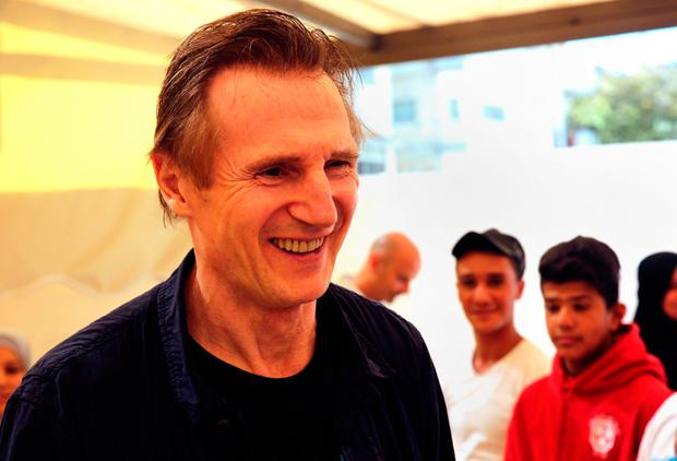 Liam Neeson listens to stories from Syrian and Jordanian students (AP Photo/Sam McNeil)