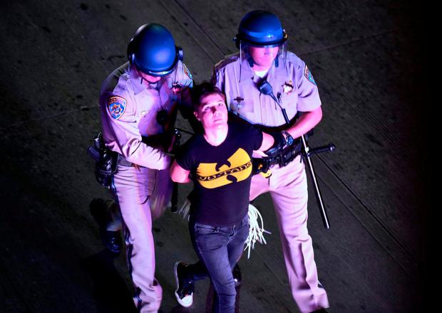 A protester who refused to leave is apprehended by California Highway Patrol officers who moved in to clear protesters off a freeway in downtown Los Angeles, California. Photo: AFP/Getty