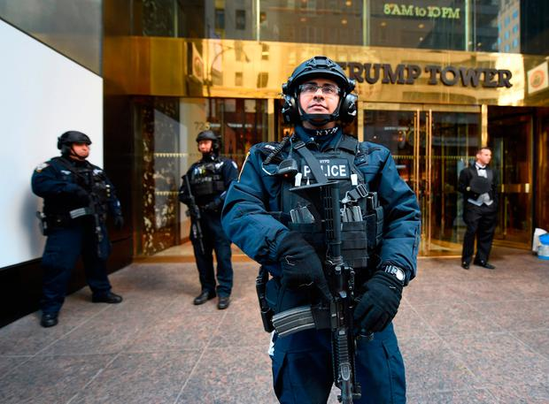 A member of the New York Police Department stands in front of Trump Tower on 5th Avenue to provide security to US President-elect Donald Trump. AFP/Getty Images