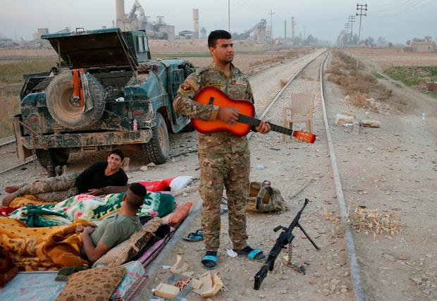 An Iraqi special forces policeman holds a guitar outside Karamah, south of Mosul, Iraq November 11, 2016. REUTERS/Goran Tomasevic