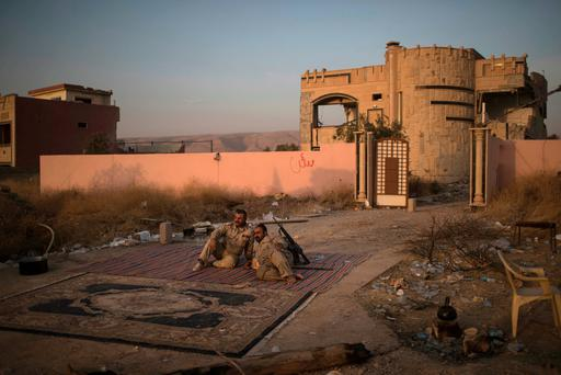 Kurdish Peshmerga fighters rest on the side of the road after taking the city from Islamic State militants in Bashiqa, east of Mosul, Iraq, Friday, Nov. 11, 2016. (AP Photo/Felipe Dana)