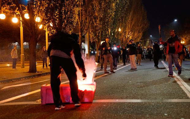 A demonstrator sets a news rack on fire as another wields a baseball bat (R) during a protest against the election of Republican Donald Trump as President of the United States in Portland, Oregon, U.S. November 11, 2016. REUTERS/William Gagan