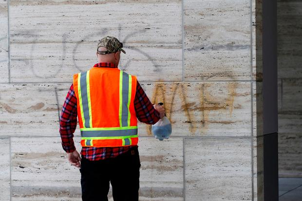Paul Watts, of Graffiti Removal Services, works for free on clean up after a protest to the election of Republican Donald Trump as President of the United States in Portland, Oregon, U.S. November 11, 2016. REUTERS/Steve Dipaola