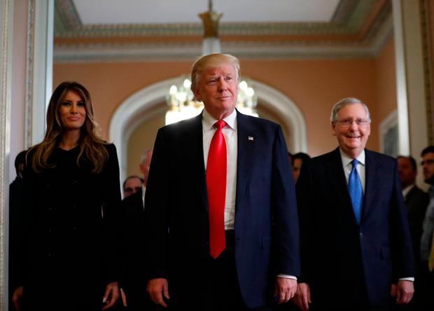 President-elect Donald Trump and his wife Melania walk with Senate Majority Leader Mitch McConnell. Photo: AP
