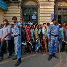 Riot police control people queueing at a bank in Old Delhi, India. Photo: Reuters