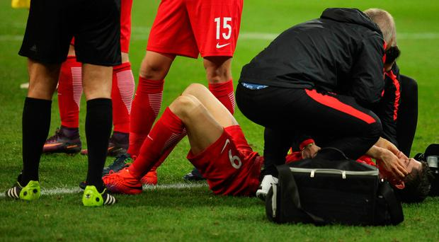 Poland's Robert Lewandowski receives medical assistance after a fire cracker went off near him